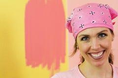 Glückliche Frau, die rosafarbene Wand malt Stockbilder