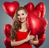 Glückliche Frau, die rotes Herz der Ballone hält Überraschung, Valentinsgrüße Leute und Valentinstagkonzept Rotes Lippenmake-up lizenzfreie stockfotografie