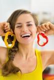 Glückliche Frau, die Scheiben des grünen Pfeffers als Ohrringe verwendet Stockfotografie