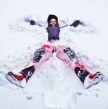 Glückliche Frau, die Schneeengel macht Stockbild