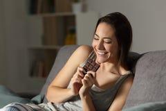 Glückliche Frau, die Schokolade in der Nacht isst stockfotos