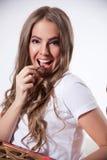 Glückliche Frau, die Schokolade isst Stockfoto