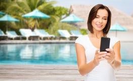 Glückliche Frau, die selfie durch Smartphone über Strand nimmt Lizenzfreies Stockfoto