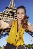 Glückliche Frau, die selfie gegen Eiffelturm in Paris, Frankreich nimmt Lizenzfreies Stockfoto