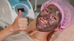 Glückliche Frau, die sich Daumen beim Haben der schwarzen Maske auf ihrem Gesicht zeigt stockfoto