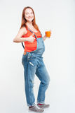 Glückliche Frau, die sich Daumen und Glas Orangensaft zeigt Stockfoto