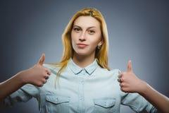 Glückliche Frau, die sich thubs zeigt Nahaufnahme-Porträtmädchenlächeln lokalisiert auf Grau Stockfotos