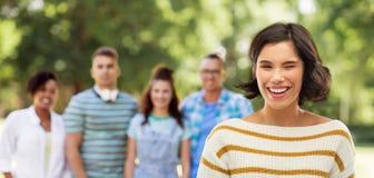 Glückliche Frau, die am Sommerpark mit Freunden blinzelt stockbilder