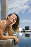 Glückliche Frau, die sonnigen Tag am Jachthafen genießt Stockbilder
