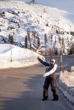 Glückliche Frau, die Straßen-Schnee per Anhalter fährt Stockbilder