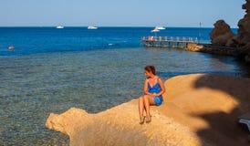 glückliche Frau, die am Strand an einem sonnigen Tag lächelt Stockfoto