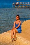 glückliche Frau, die am Strand an einem sonnigen Tag lächelt Lizenzfreie Stockfotografie