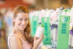 Glückliche Frau, die tägliche Lebensmittelergänzungen in einem Speicher auswählt Lizenzfreies Stockfoto