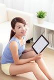 Glückliche Frau, die Tabletten-PC auf Sofa verwendet Stockfotos