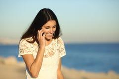 Glückliche Frau, die am Telefon geht auf den Strand spricht lizenzfreies stockfoto