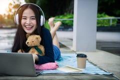 Glückliche Frau, die unten liegt, arbeitend mit Laptop-Computer attraktiv stockfotografie