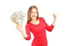 Glückliche Frau, die US-Dollars hält und Glück gestikuliert Lizenzfreie Stockfotografie