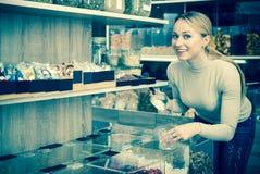 Glückliche Frau, die verschiedene kandierte Früchte vorwählt Lizenzfreie Stockbilder