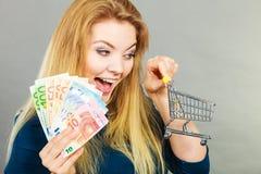 Glückliche Frau, die Warenkorb mit Geld hält Lizenzfreie Stockfotos