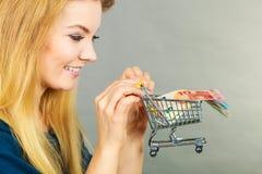 Glückliche Frau, die Warenkorb mit Geld hält Stockfoto