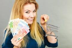Glückliche Frau, die Warenkorb mit Geld hält Lizenzfreies Stockbild