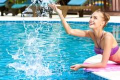 Glückliche Frau, die Wasser im Pool spritzt Lizenzfreies Stockbild