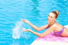 Glückliche Frau, die Wasser im Pool spritzt Stockfotografie