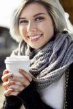 Glückliche Frau, die Wegwerfkaffeetasse an der Bahnstation hält Lizenzfreie Stockfotos