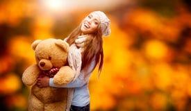 Glückliche Frau, die weichen Bären über Herbsthintergrund hält Stockfoto