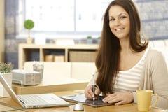 Glückliche Frau, die Zeichnungsauflage verwendet Lizenzfreie Stockbilder