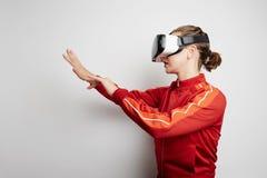 Glückliche Frau, die zu Hause Erfahrung unter Verwendung der VR-Kopfhörergläser virtueller Realität viel gestikulierende Hände er Lizenzfreie Stockfotos