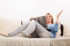 Glückliche Frau, die zu Hause Laptop auf der Couch verwendet Lizenzfreies Stockbild