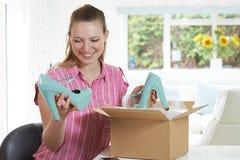 Glückliche Frau, die zu Hause on-line-Kauf auspackt Lizenzfreie Stockbilder