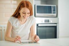 Glückliche Frau, die zu Hause unter Verwendung der digitalen Tablette auf Schreibtisch arbeitet lizenzfreies stockfoto