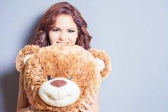 Glückliche Frau empfing einen Teddybären an der Feier Stockfoto