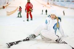 Glückliche Frau fällt auf Ski Stockfotos