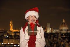 Glückliche Frau in Florenz, Italien mit dem Weihnachtsgeschenk, das beiseite schaut Lizenzfreies Stockfoto