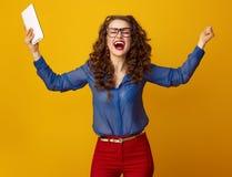 Glückliche Frau gegen gelben Hintergrund mit dem Tablet-PC-Freuen Stockfotos