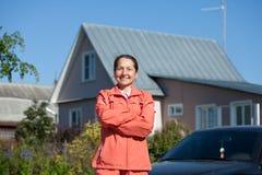Glückliche Frau gegen Haus Stockbild