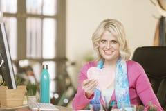 Glückliche Frau in ihrem Büro mit Valentine Heart Stockbilder