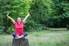 Glückliche Frau in ihrem 50s, das auf einem Baumstumpf sitzt Lizenzfreie Stockfotografie