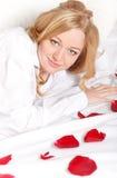 Glückliche Frau im Bett mit den Rosen-Blumenblättern Stockbilder