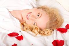 Glückliche Frau im Bett mit den Rosen-Blumenblättern Lizenzfreies Stockfoto