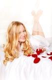 Glückliche Frau im Bett mit den Rosen-Blumenblättern Stockfoto