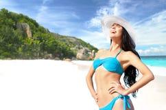 Glückliche Frau im Bikini- und Sonnenhut auf Strand Stockfotos