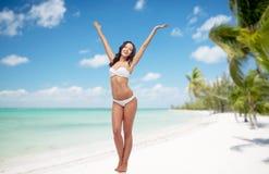 Glückliche Frau im Bikinibadeanzugtanzen auf Strand Stockfoto