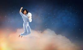 Glückliche Frau im blauen Pyjama, der mit Kissen springt lizenzfreie stockfotografie