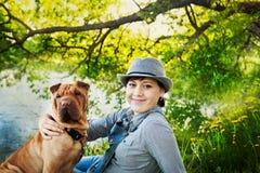 Glückliche Frau im Denimoverall und Hut mit ihrem Hund Shar Pei, der in der Wiese nahe dem See bei Sonnenuntergang sitzt stockfoto