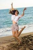 Glückliche Frau im Jump-Shot am Strand Lizenzfreie Stockfotos