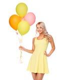 Glückliche Frau im Kleid mit Heliumluftballonen lizenzfreies stockbild